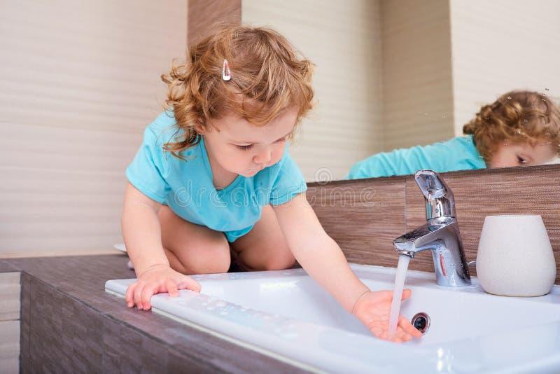 洗她的手的小女孩在卫生间里 免版税库存照片