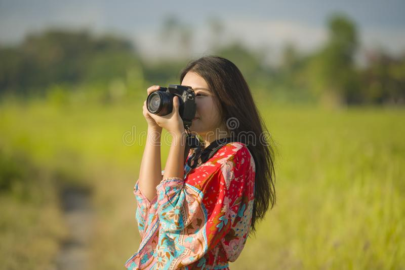 她的拍与照片照相机微笑的20s的甜年轻亚裔中国或韩国妇女照片愉快在美好的自然风景 库存照片