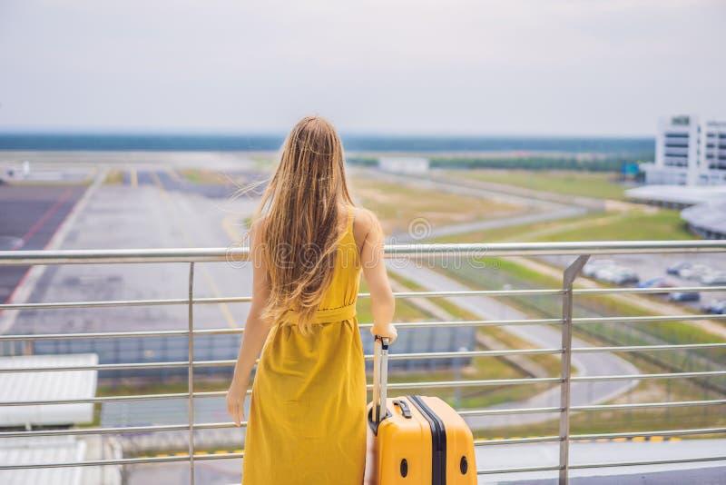 她的旅途开始  在一件黄色礼服和一个黄色手提箱的美好的年轻女人ltraveler等待她的飞行 免版税库存照片