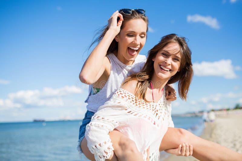 给她的朋友肩扛的海滩的愉快的妇女 库存照片