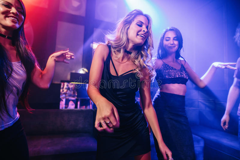 她的朋友围拢的年轻clubber跳舞 免版税图库摄影
