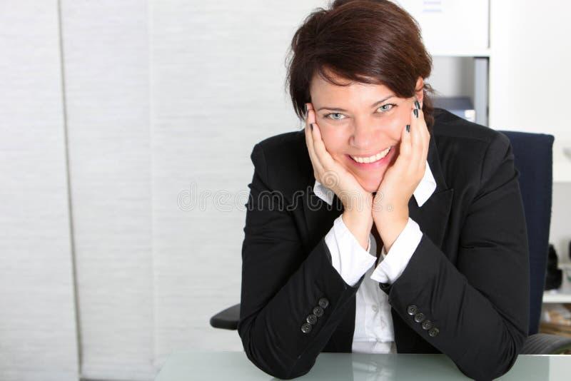 她的服务台的微笑的企业专业人员 免版税图库摄影