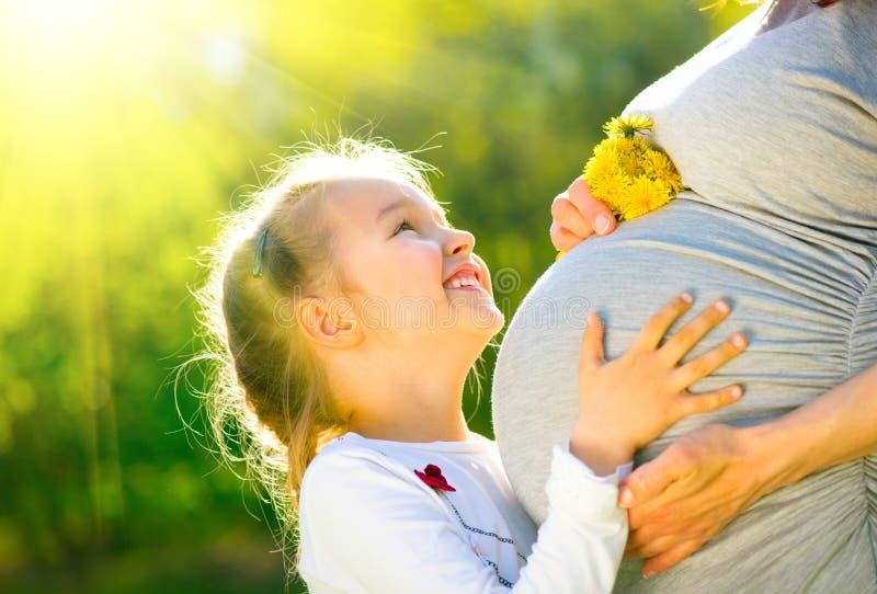 她的母亲的腹部的小孩听的婴孩室外在晴朗的自然 有她的小女儿的愉快的怀孕的母亲 免版税库存照片