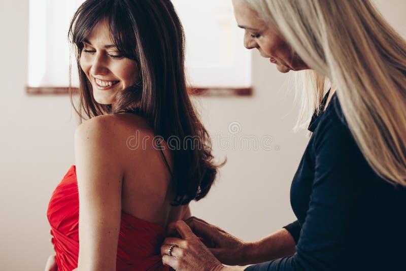 她的母亲被帮助的一名微笑的妇女的侧视图 把勾子放的年长妇女在少女的礼服上 免版税库存图片
