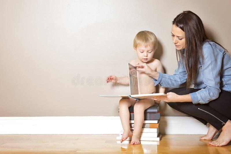 她的母亲读取儿子 免版税库存照片