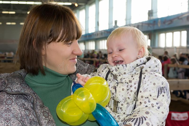 她的母亲` s胳膊的一个小孩子拿着一个气球并且笑 免版税库存照片