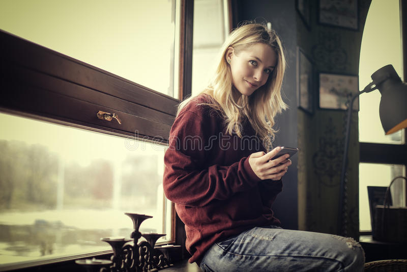 她的电话的微笑的妇女 免版税库存图片