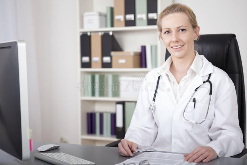 她的看照相机的书桌的女性医师 库存图片