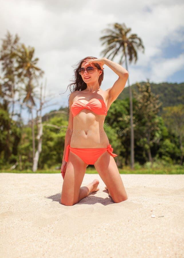 她的膝盖的年轻女人在海滩沙子,遮蔽她的眼睛从太阳,绿色棕榈密林在背景中 免版税库存照片