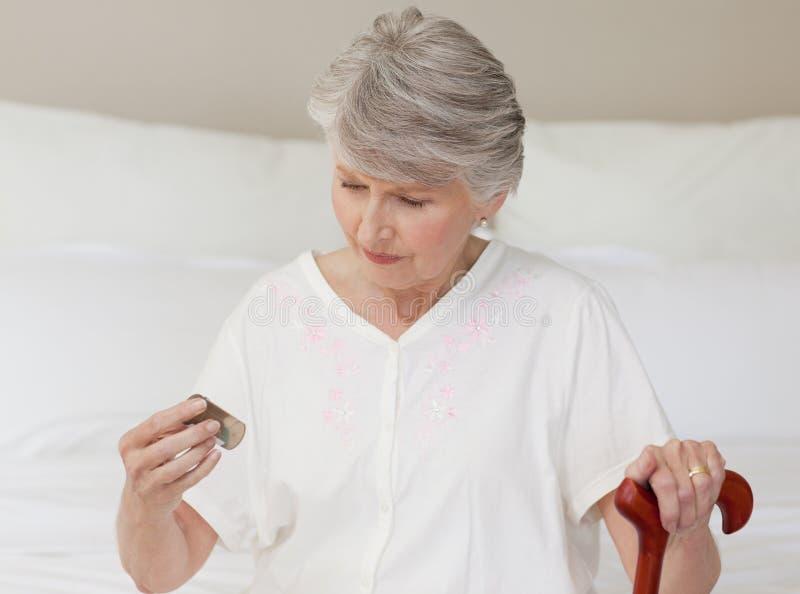 她的药片高级病的采取的妇女 免版税库存图片