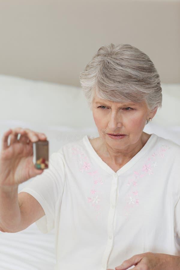 她的药片高级病的采取的妇女 免版税库存照片