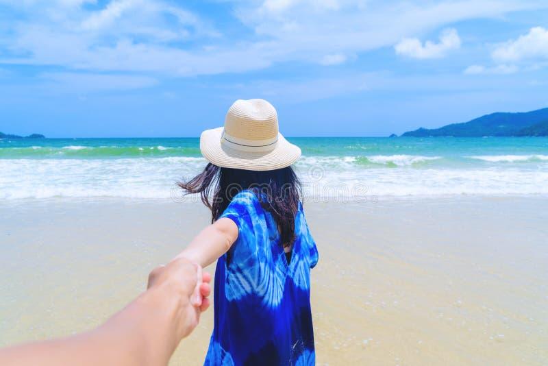 她的蜜月的男朋友的愉快的亚洲妇女藏品手在海滩在旅行假日期间在海洋假期户外或 免版税图库摄影