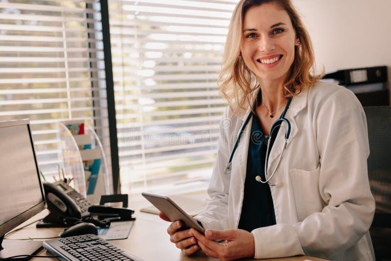她的诊所书桌的友好的女性医生 图库摄影