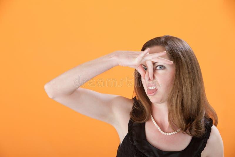 她的鼻子捏妇女 免版税图库摄影