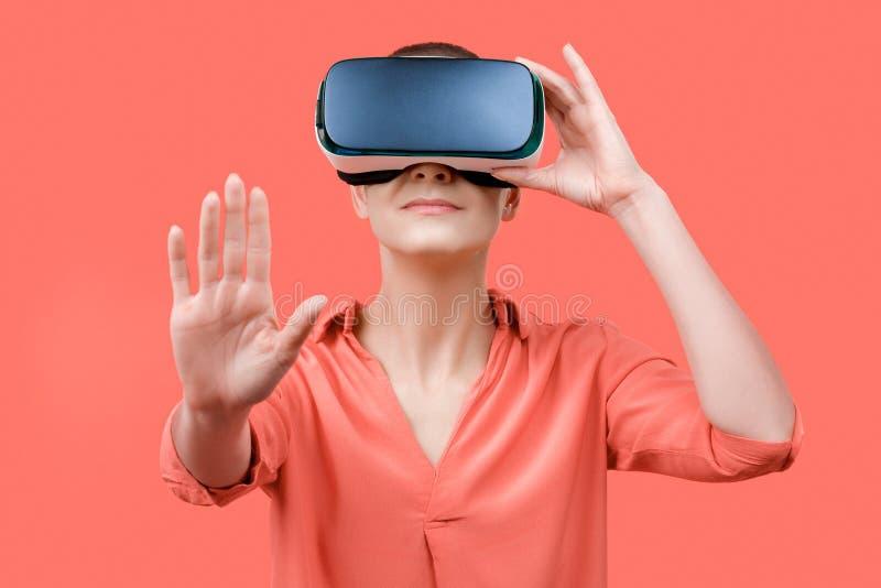 她的30s的年轻女人使用虚拟现实风镜 佩带在珊瑚背景的妇女VR耳机 Vr?? 免版税库存图片