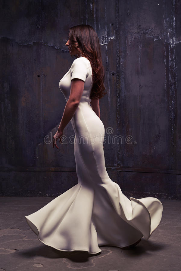 她礼服流动惊人的妇女的侧视图走和 免版税图库摄影