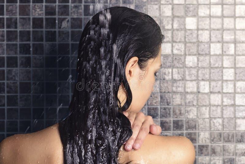 洗她长的头发的少妇在阵雨下 免版税库存照片