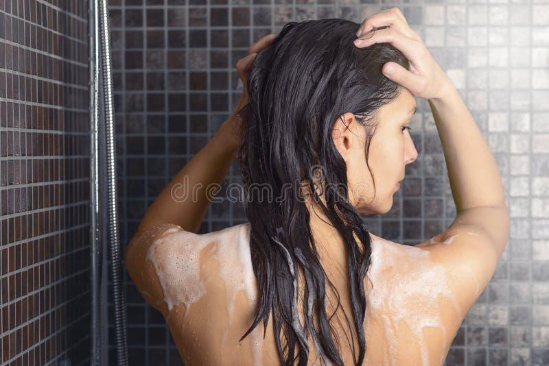 洗她长的头发的少妇在阵雨下 库存照片