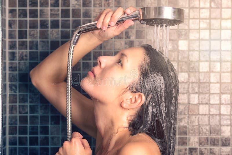 洗她长的头发的少妇在阵雨下 免版税库存图片