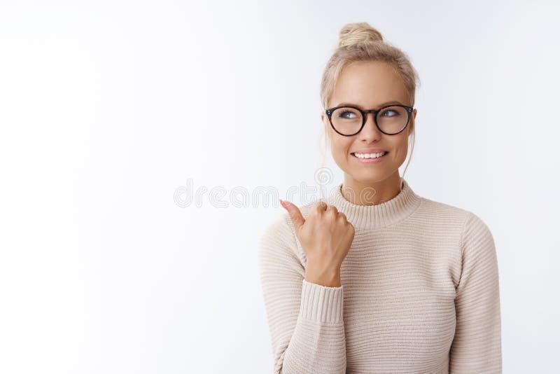 好主意来了女孩头脑 迷住作为看创造性和被吸引的玻璃微笑的厚脸皮和时髦的白肤金发的妇女 库存图片