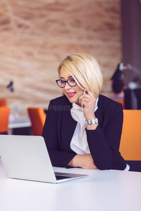 好企业谈话 玻璃的快乐的年轻美丽的妇女谈话在手机和使用膝上型计算机的 库存图片