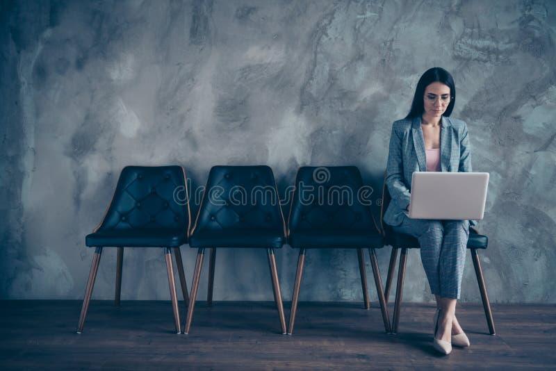 好典雅的时髦的时髦别致豪华高级主管经理深色的夫人等待的任命键入的电子邮件 免版税库存图片