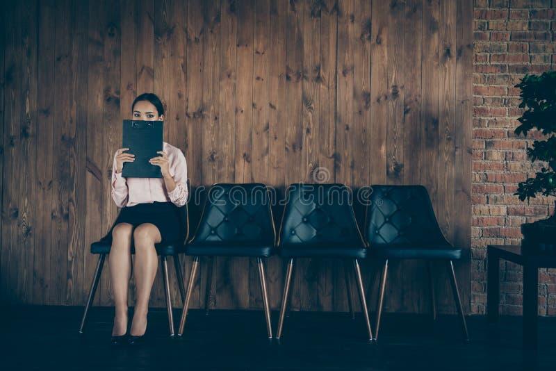好可爱的典雅的夫人合格的专家画象坐椅子等待的会议征兵人员掩藏的面孔 免版税库存图片
