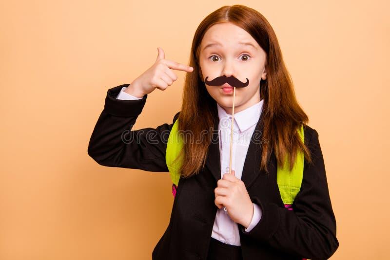 好可爱的可爱的幼稚嬉戏的青春期前的展示伪造品的女孩佩带的夹克燃烧物特写镜头画象  免版税库存图片