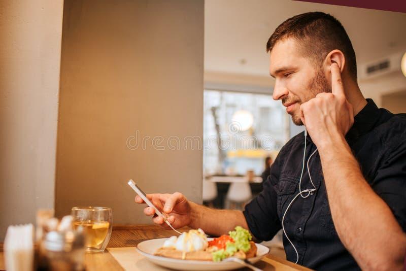 好和可爱的人在他的手上坐在tabel并且拿着电话 他听到音乐通过耳机 人 免版税库存照片