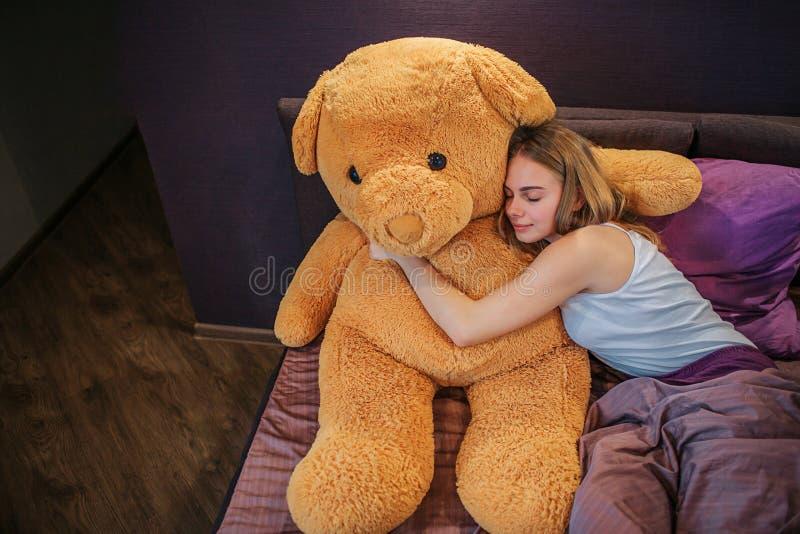 好和有吸引力的年轻女人睡眠 她拥抱大误码率玩具高兴地 妇女用丝绸部分盖 免版税库存照片