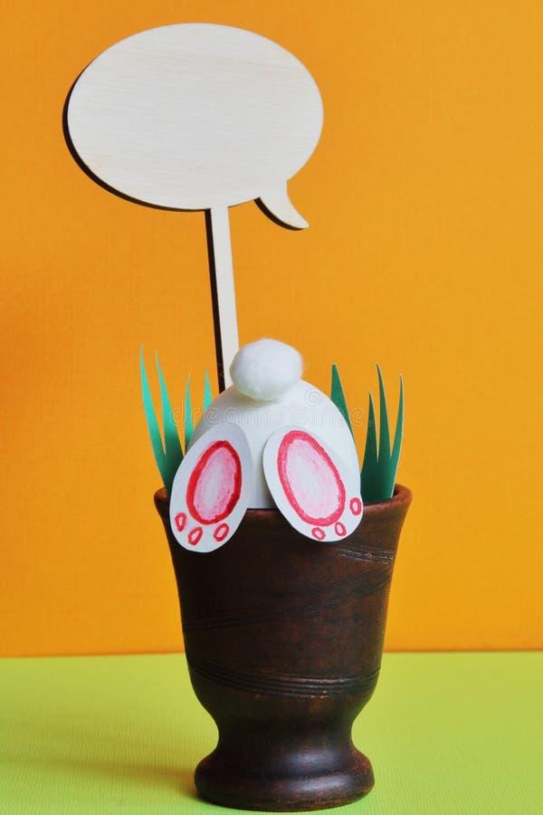 好奇复活节兔子,在陶瓷花瓶的轻便短大衣有绿草的由纸制成在明亮的不同的背景 最小的概念为 免版税库存照片