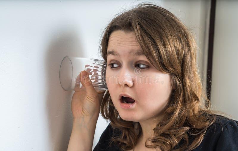 好奇少妇是听和暗中侦察在墙壁后的邻居 免版税图库摄影