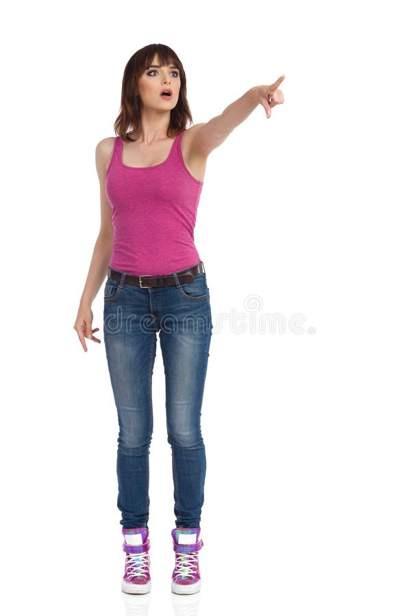 好奇年轻女人看和指向 库存照片