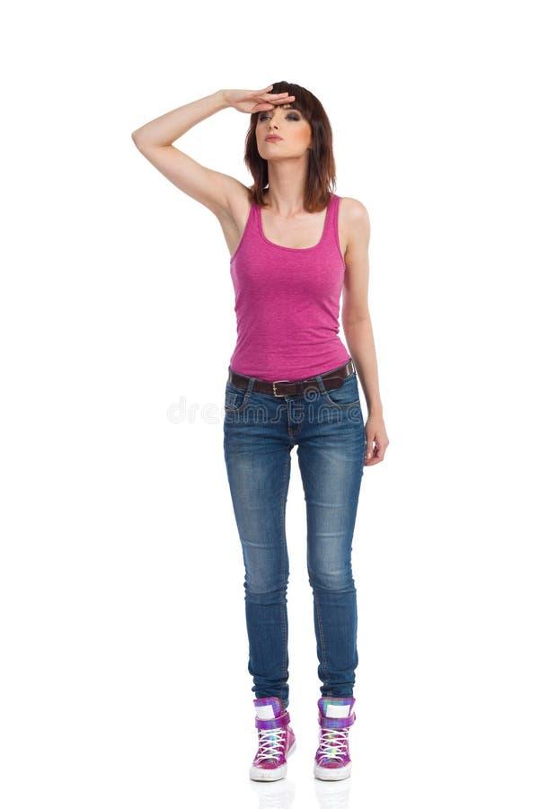 好奇年轻女人站立,握在前额和观看的手 免版税库存图片