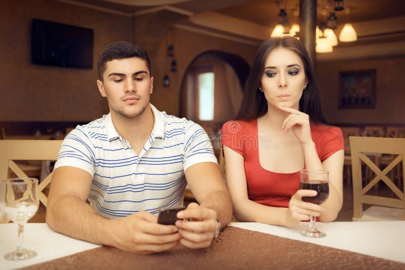 好奇智能手机的女孩暗中侦察的男朋友 库存图片