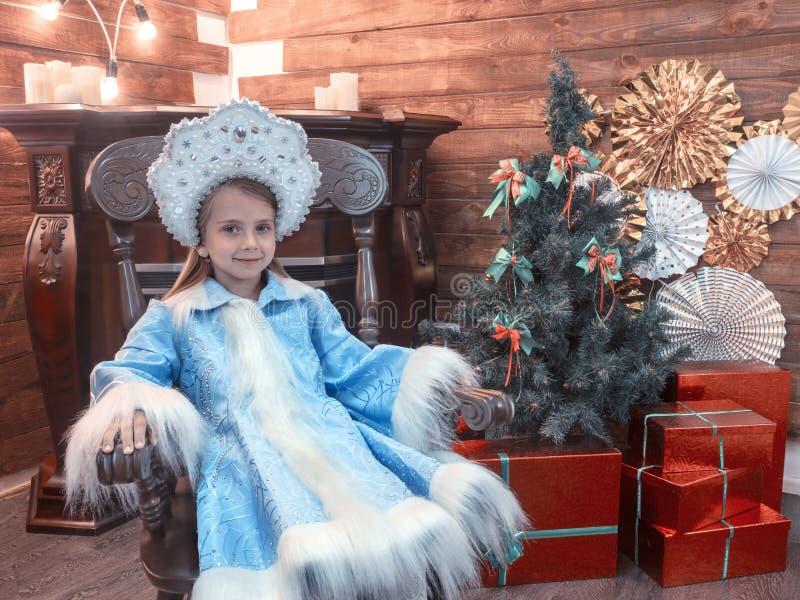 好女孩在一把木椅子坐 免版税库存图片