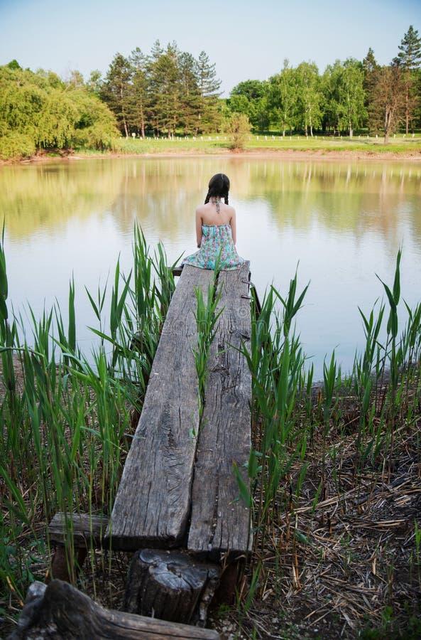 好女孩坐的前面湖 免版税库存照片