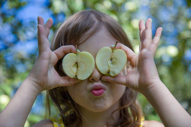 好女孩用半苹果 在自然本底 免版税图库摄影