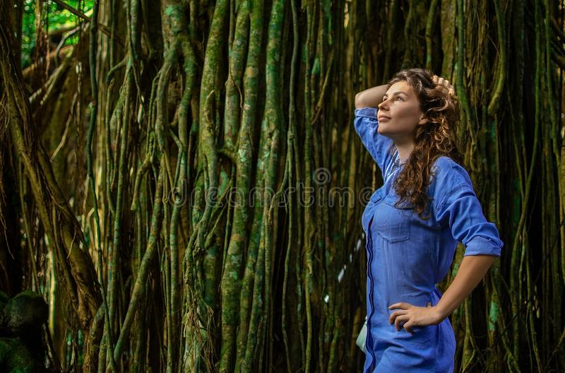 好年轻女人画象在有lians的密林拍照片 女孩支持在她旁边的树 的treadled 库存照片