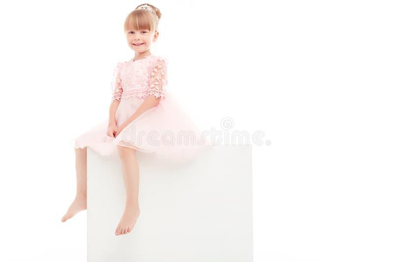 好微笑的女孩坐白色箱子 免版税图库摄影