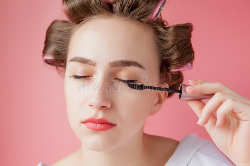 好快乐年轻卷发的人的女孩绘在桃红色背景的眼眉 免版税库存图片