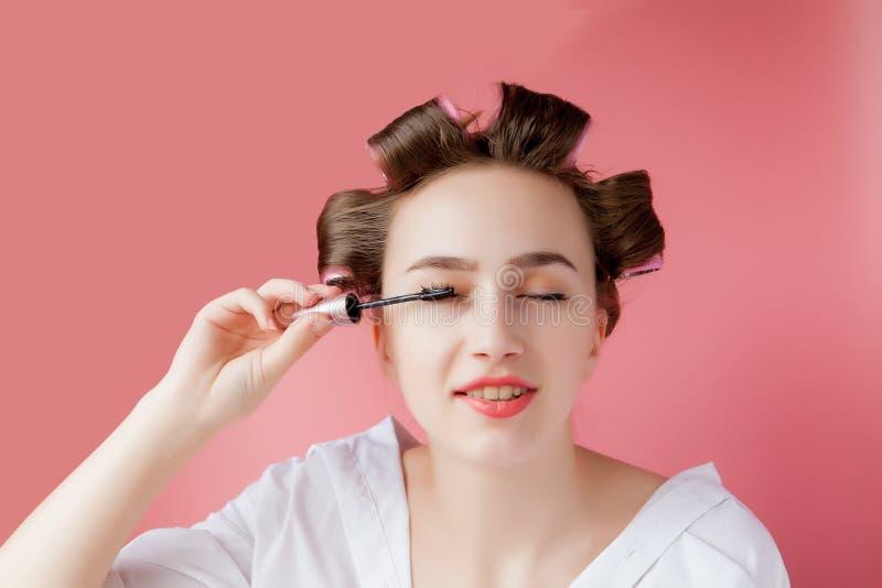 好快乐年轻卷发的人的女孩绘在桃红色背景的眼眉 免版税图库摄影