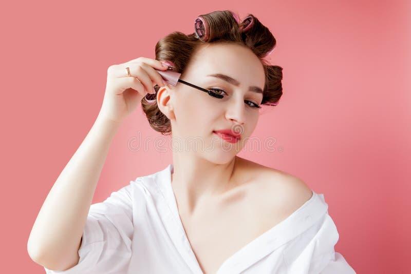 好快乐年轻卷发的人的女孩绘在桃红色背景的眼眉 免版税库存照片