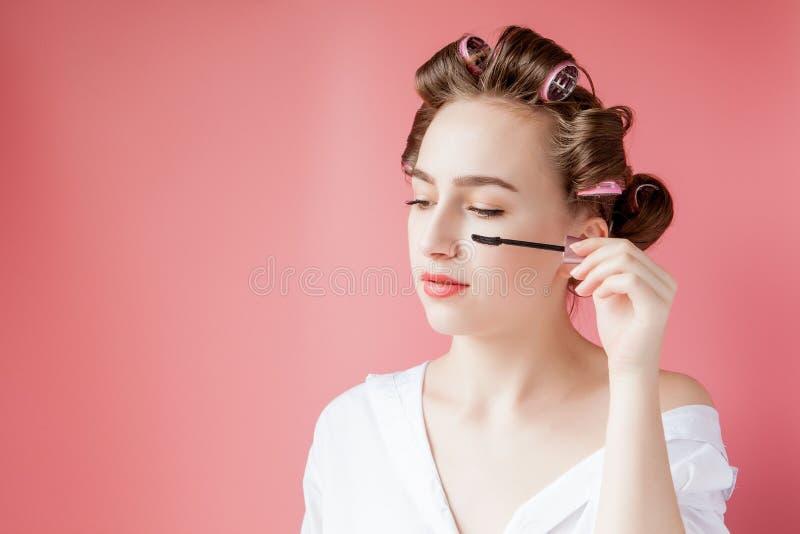 好快乐年轻卷发的人的女孩绘在桃红色背景的眼眉 库存照片