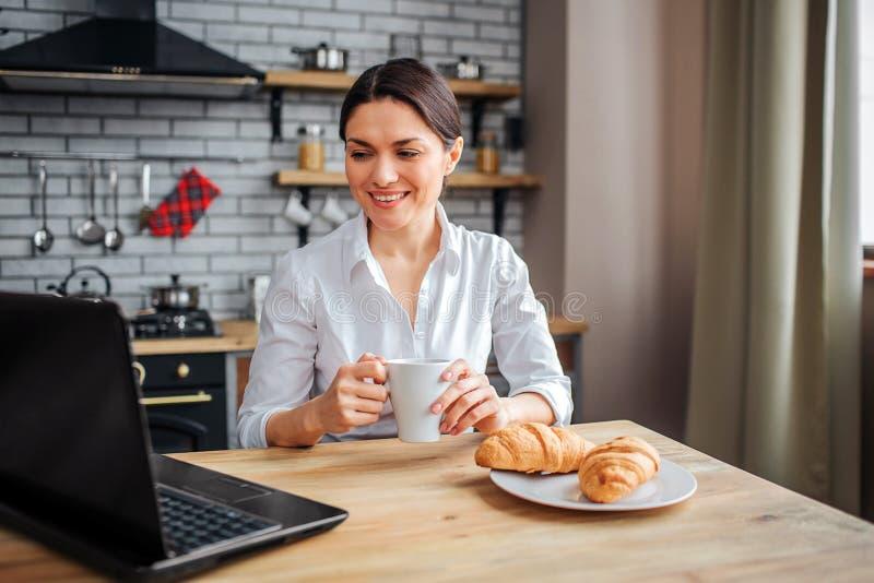 好快乐的女实业家坐在桌在厨房里和神色上在膝上型计算机 她在家工作 式样举行白色杯子与 库存照片