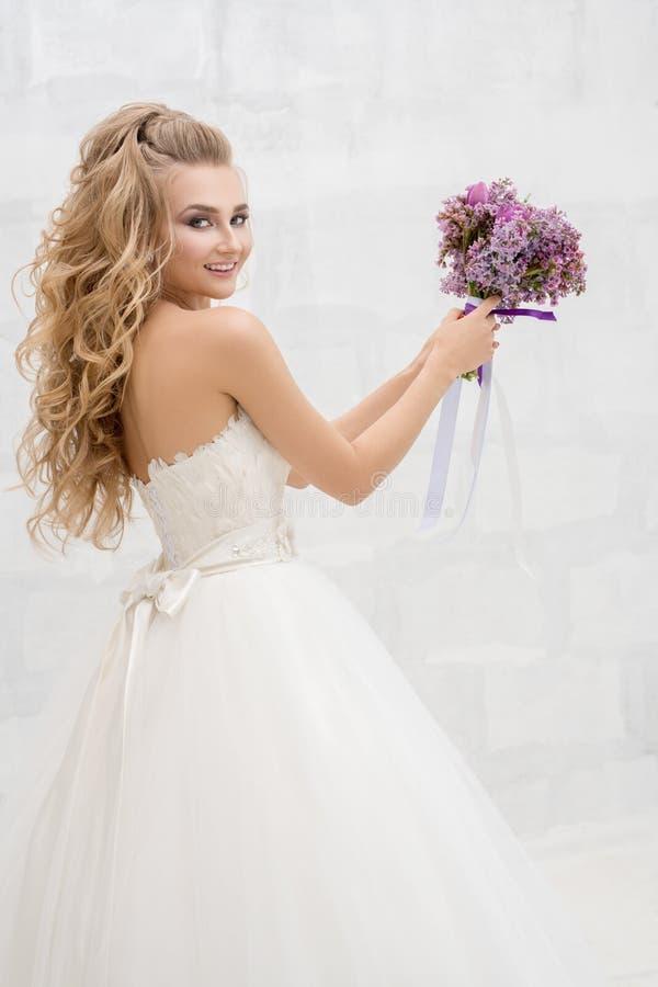 年轻好新娘在投掷她的花束的演播室 免版税库存图片