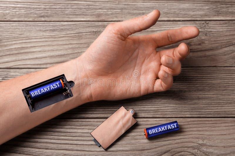 好早餐整天加强 人的手有槽孔的有早餐的充电的电池的 免版税库存照片