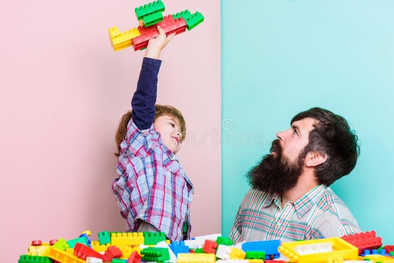 好更高的手段 愉快的家庭休闲 有一起使用的爸爸的小男孩 儿童发育 修造的飞机与 库存照片