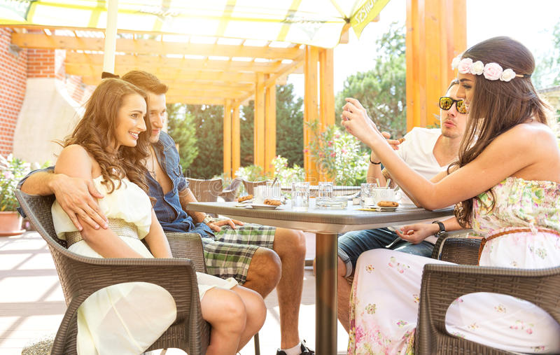 好朋友在大阳台谈话,做†‹â€ ‹与手机的一张好照片 免版税库存图片
