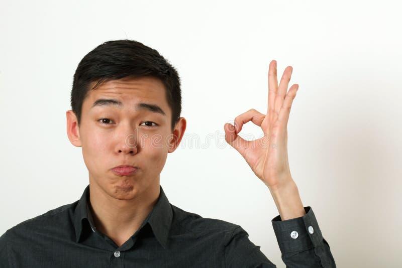 给好标志和看加州的满意的年轻亚裔人 免版税库存照片